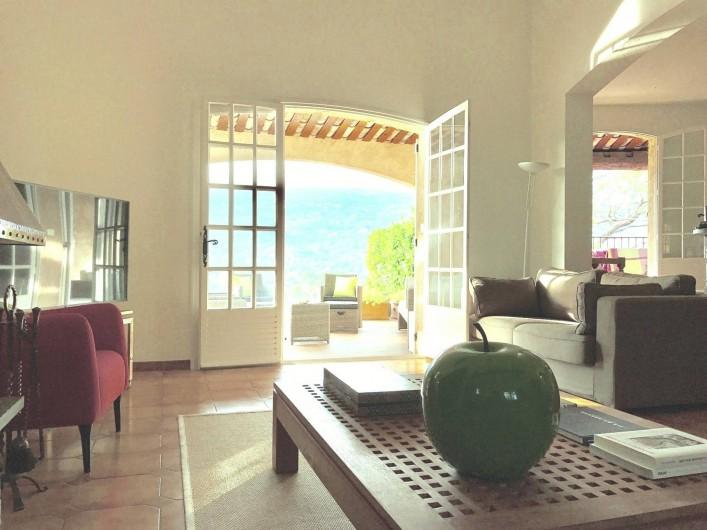 Location de vacances - Villa à Peymeinade - salon/salle à manger. Vue sur terrasse couverte
