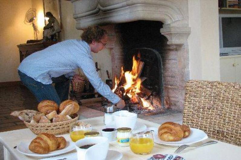 Location de vacances - Chambre d'hôtes à Beaune - Vincent prépare le petit déjeuner au bord de la cheminée, en hiver.