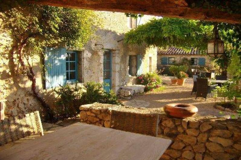 """Location de vacances - Mas à Mons - terrasse couverte, table sous la tonnelle, au fond la """"petite maison"""""""