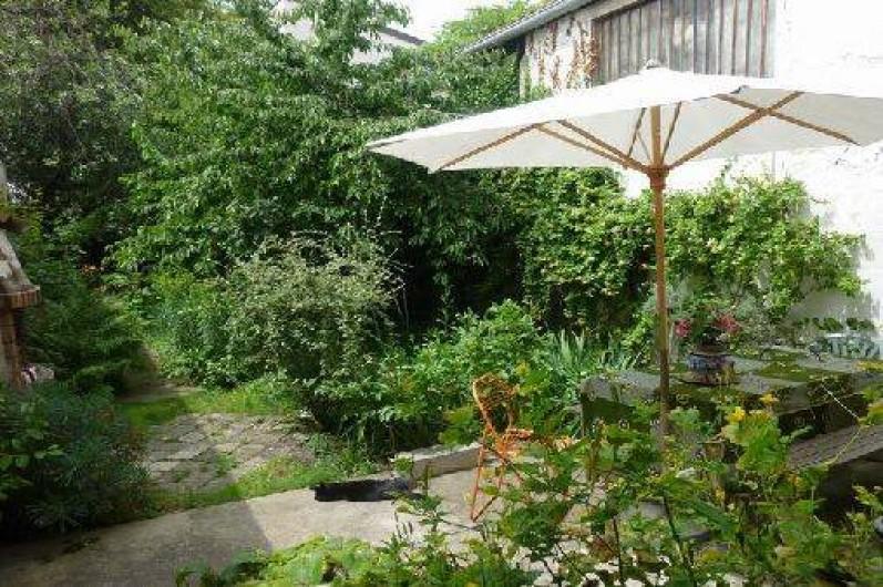 Location de vacances - Villa à Montreuil - terrasse dans le jardin avec barbecue en pierre et meubles de jardin