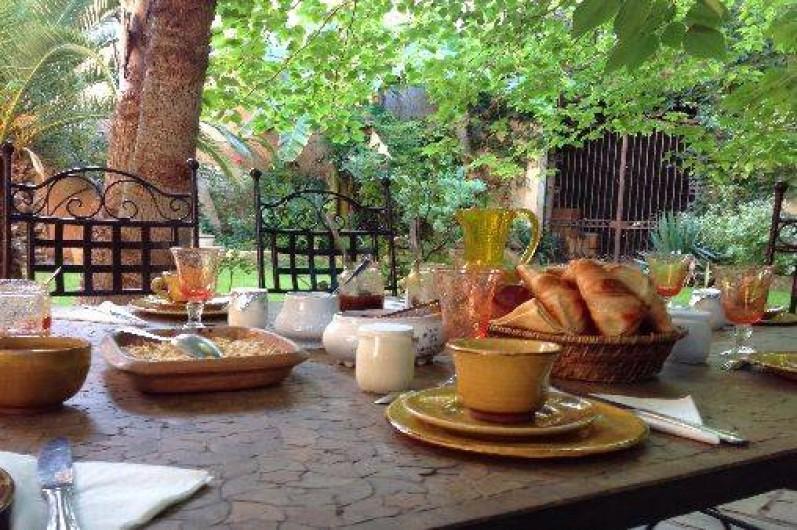 Location de vacances - Chambre d'hôtes à Fabrègues - Une vue gourmande du petit-déjeuner à l'ombre des palmiers.