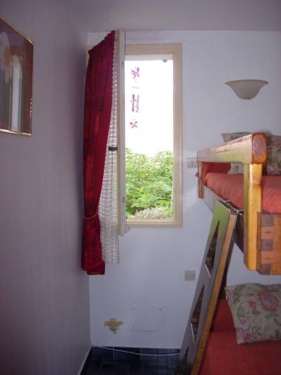 Location de vacances - Appartement à Le Cap d'Agde - chambre 2 , 2 lits superposés 1 place. Fenêtre vu cheminement extérieur et park.