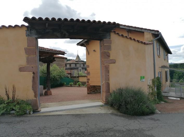 Location de vacances - Gîte à Pomeys - Le portail d'entrée de la cour privative avec le gîte à droite .